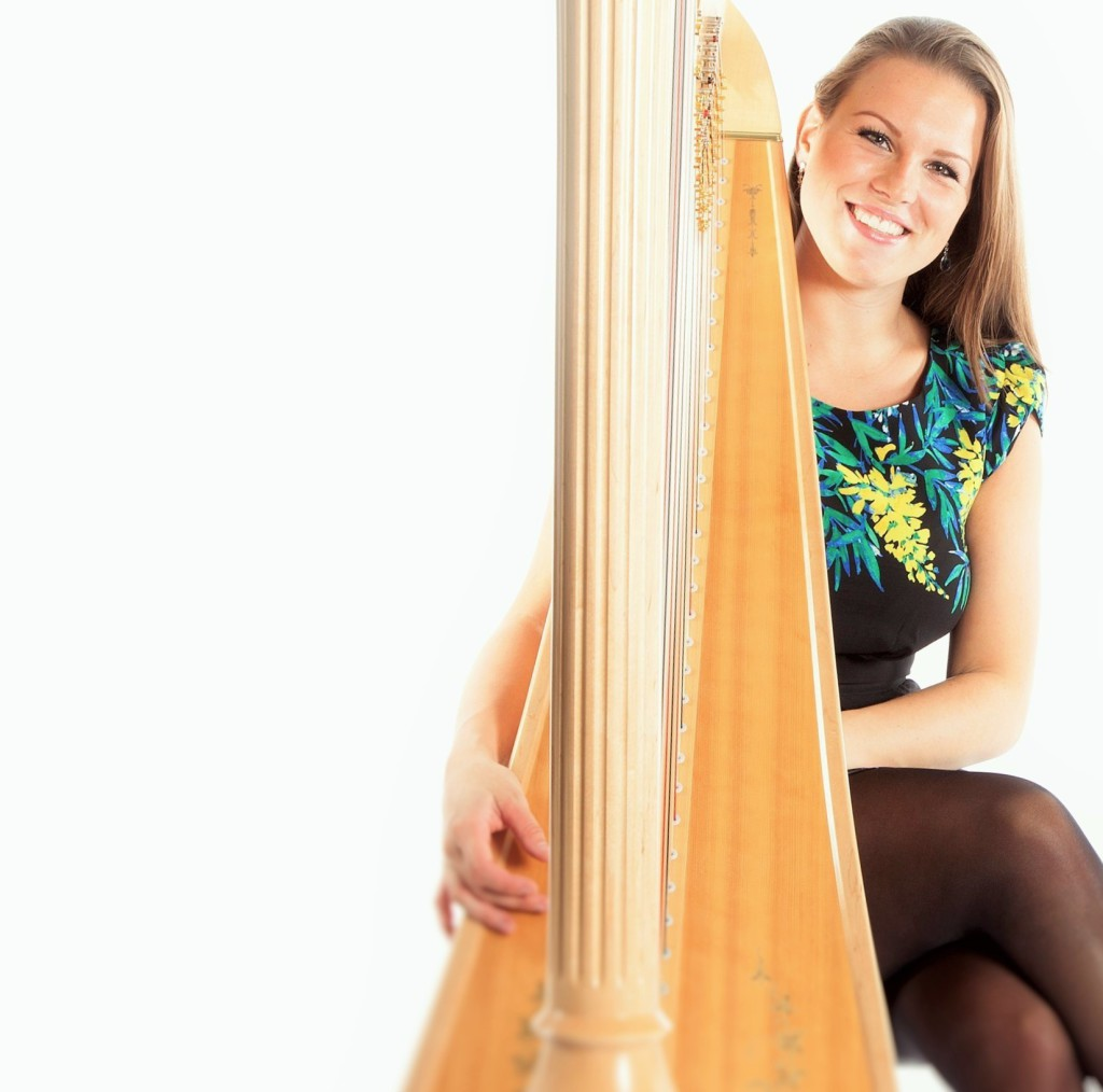 young caucasian woman sits behind concert harp in studio against