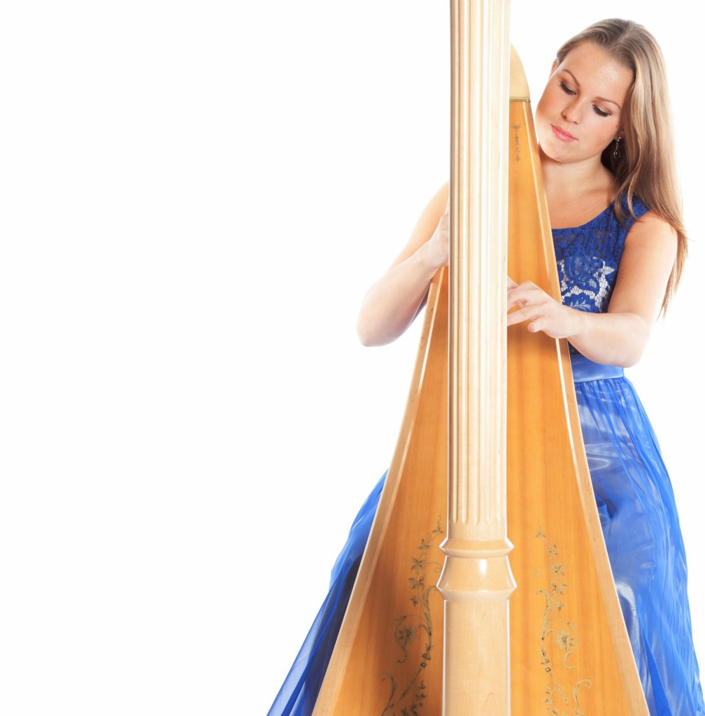 young caucasian woman sits and plays concert harp in studio agai