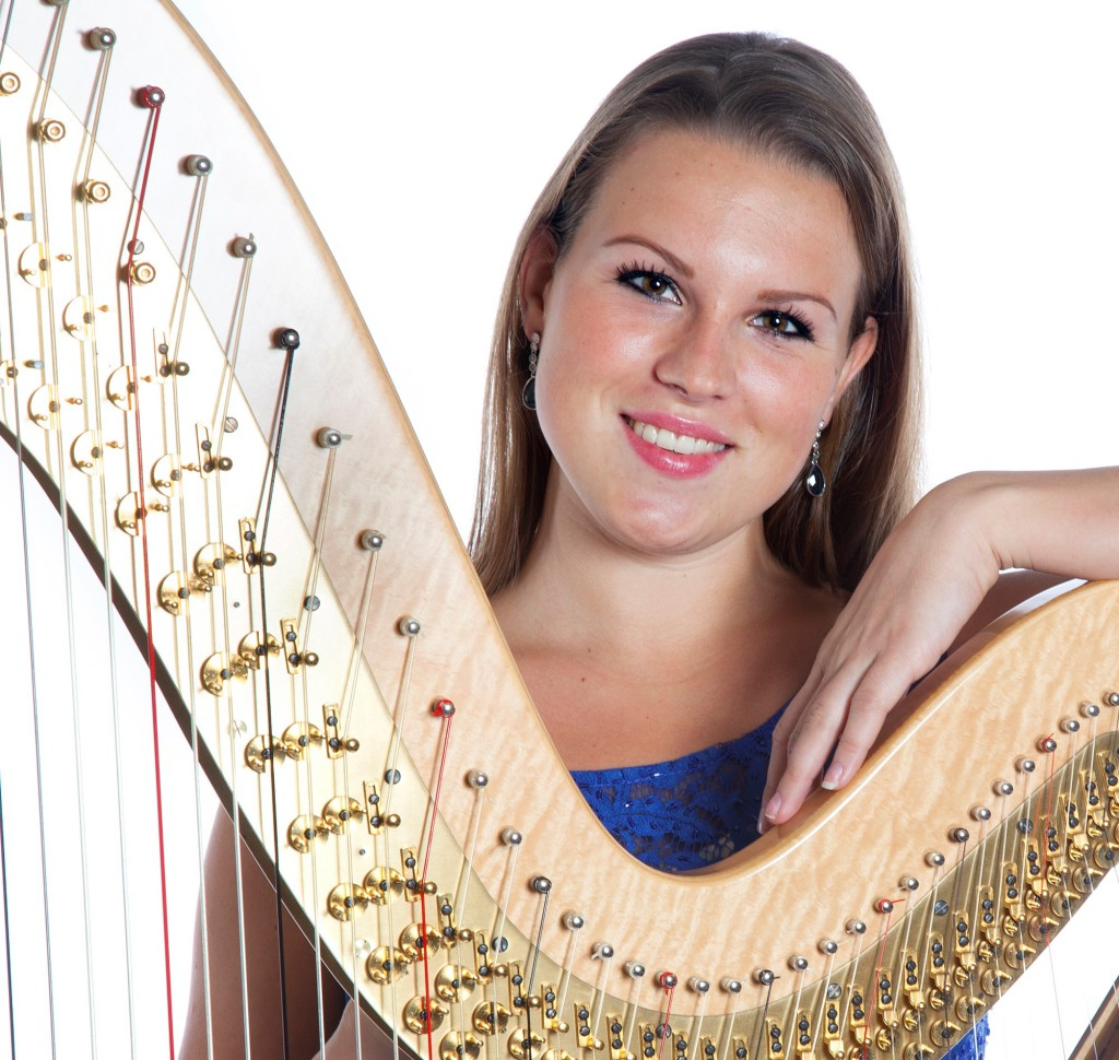young caucasian woman with concert harp in studio against white