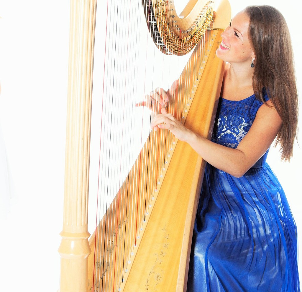 two young women in studio with harp and clarinet against white b